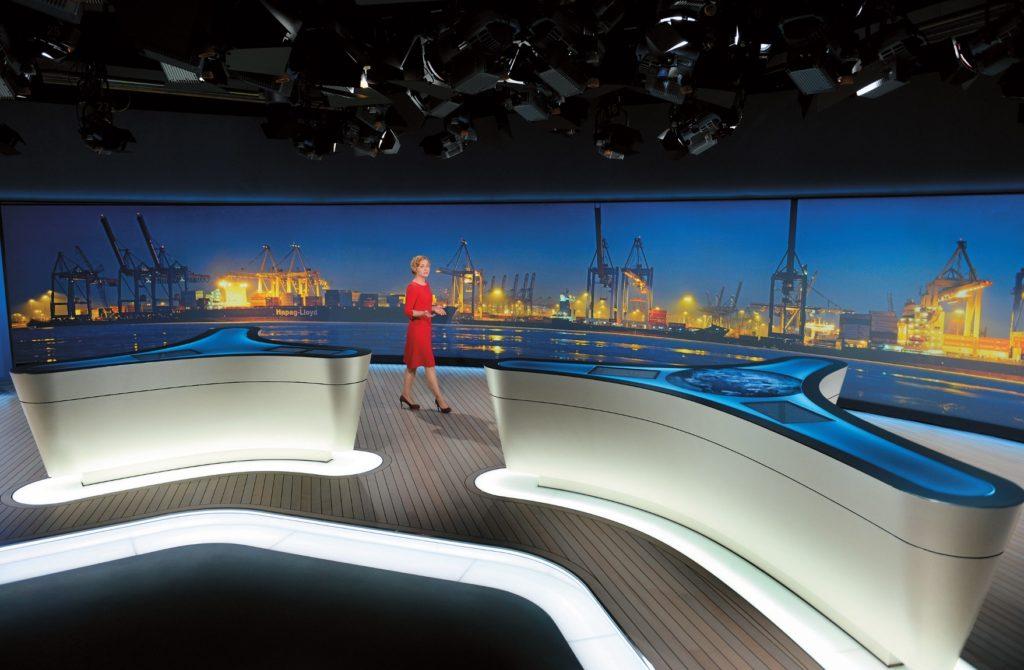 """Die Moderatorentische sind Unikate, die in einem Stück von den hauseigenen Werkstätten des NDR gefertigt wurden. Sie mussten in das Studio transportiert werden, bevor die gewaltige Medienwand den Studiozugang für sperrige Materialien """"zubaut""""."""