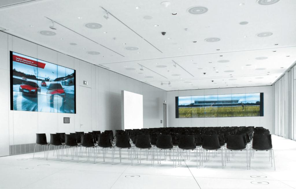 Komplett geöffneter Konferenzbereich mit zwei Monitorwänden (Quelle: Audi)