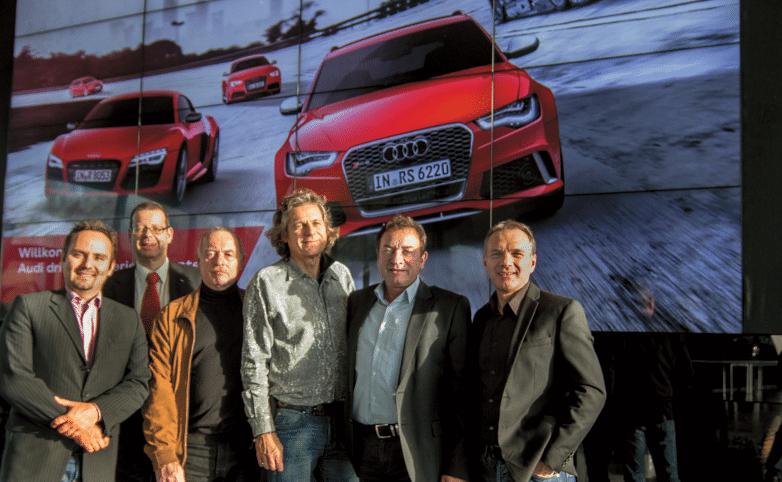 Das Projekt-Team: Sascha Jilko & Wolfgang Vogt (Audi), Hans-Peter Hofmann & Achim Hannemann (hp+Plan), Michael Krämer & Jörg Alberti (BFE) vor der Monitorwand bei voller Sonneneinstrahlung von der Seite