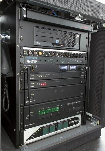 Medientechnikrack in einem Seminarraum; links ist der Hörer des IP-Telefons zu erkennen