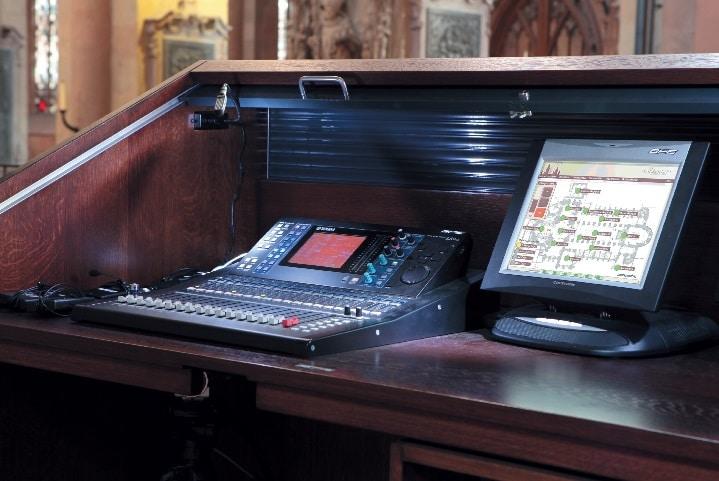 Regietisch nahe des Altars mit Yamaha LS9 und Crestron Touchpanel. Einzelne Lautsprecherpositionen sind per Fingerdruck ein- oder auszuschalten – für Übersicht sorgt ein Grundriss des Doms, auf dem die einzelnen Positionen als Punkte markiert sind – je nach Aktivität grün oder rot.