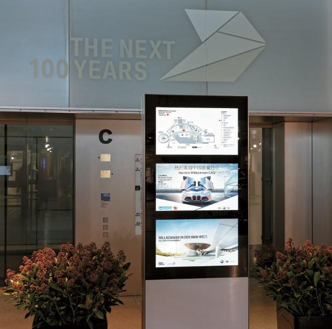 An den Aufzügen wird an schlanken Stelen auf drei Bildschirmen ein Lageplan angezeigt sowie auf aktuelle Veranstaltungen hingewiesen. Allerorts zu sehen ist ein Willkommensgruß an die Besucher.