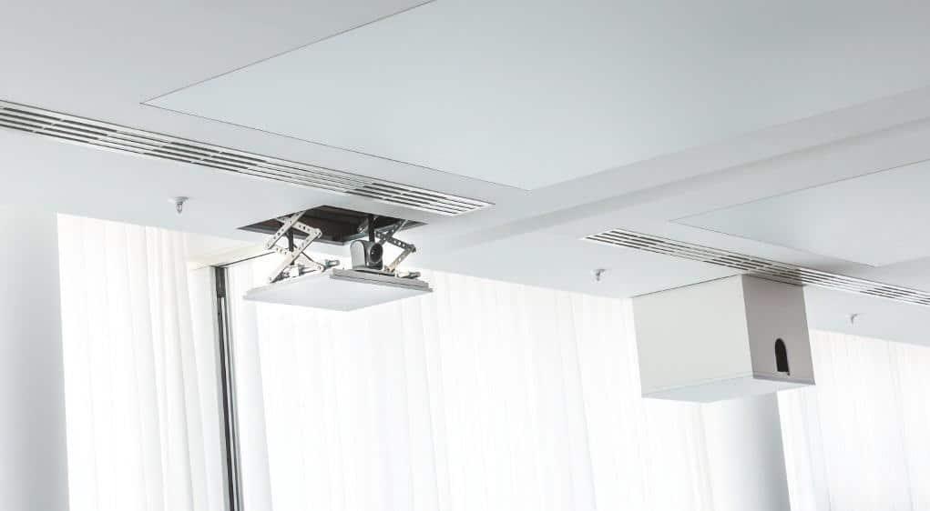 Projektoren lassen sich im Großen Konferenzsaal bei Bedarf aus der Decke ausfahren. Die Kamera des Polycom Videokonferenzsystems ist ebenfalls an einem Audipack-Deckenlift befestigt. Kanzlei Flick Gocke Schaumburg