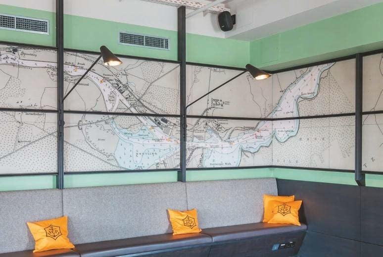 MASK4C-Lautsprecher ohne sichtbare Anschlusskabel im Club-Raum, unten rechts ist ein in die Sitzbank eingelassenes Anschlussfeld