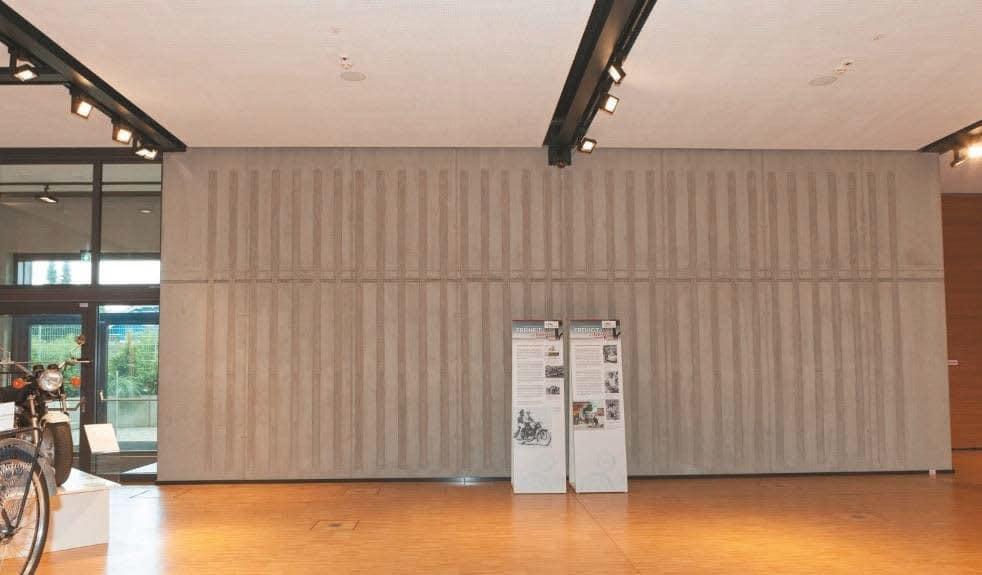 Die Rückwand ist vertikal leicht strukturiert und hat in die Betonwand integrierte, schallabsorbierende Flächen