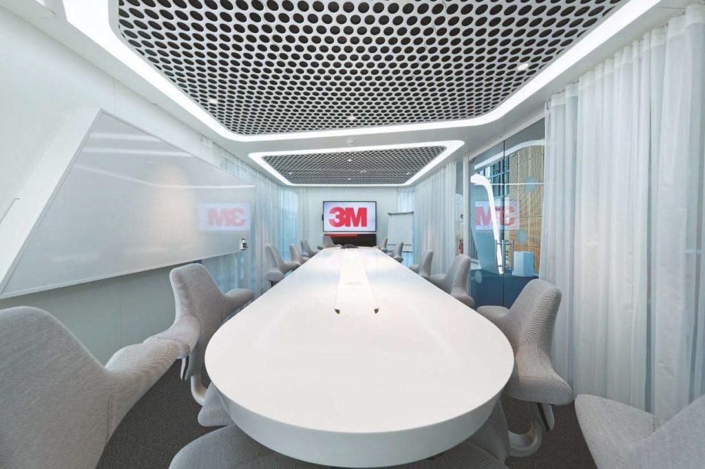"""Zentrales Element des """"Collaboration Room"""" ist ein langer weißer Tisch, der mit drei RFID-Leseflächen sowie hinter Klappen verborgenen Anschlussfeldern ausgestattet ist."""