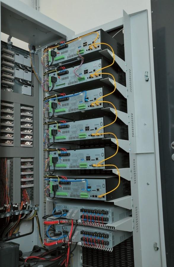 Ein Blick in den geöffneten Schrank mit sechs Endstufen (oben) und den 24 V Notstrom-Managern (unten)