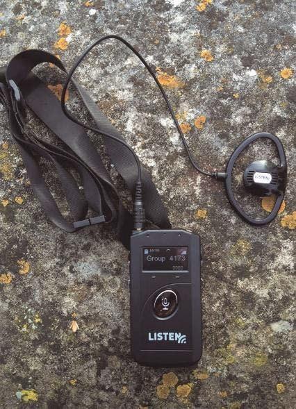 Der ListenTALK-Transceiver mit Ohrhörer und Tragband beim Einsatz