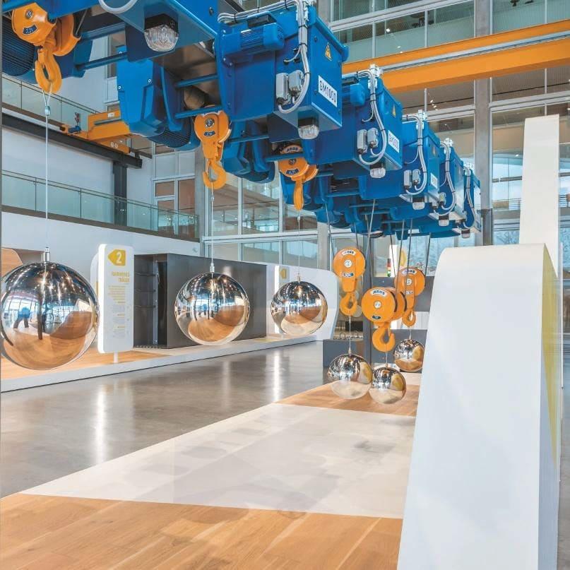 Sechs unterschiedlich leistungsstarke Elektroseilzüge samt daran befestigten Spiegelkugeln
