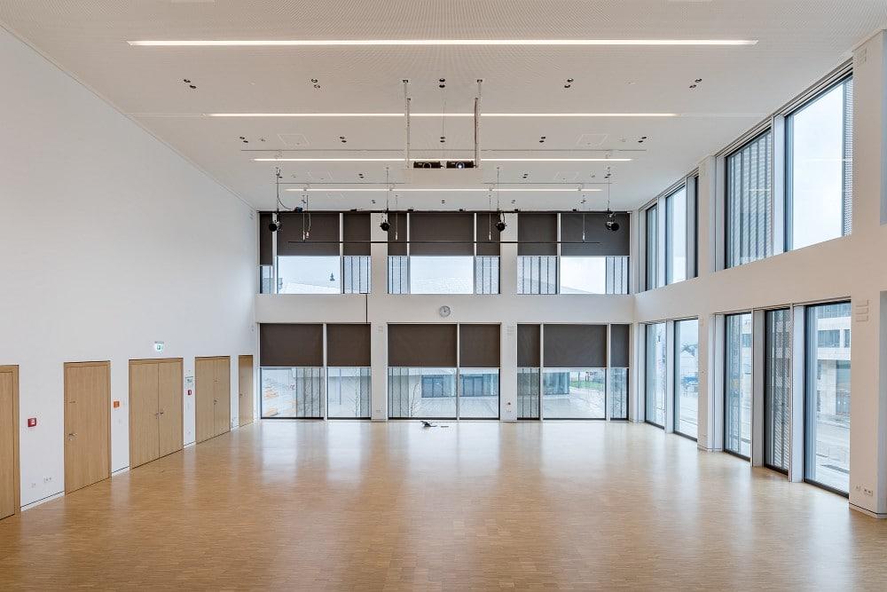 Hohe Fensterfronten lassen auf Wunsch viel Tageslicht in den Großen Saal. Zur Ausstattung gehören zwei Panasonic-Projektoren an der Decke.