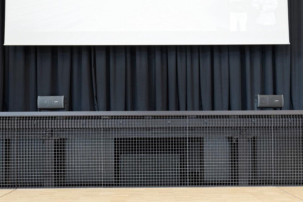 Je nach Veranstaltungssituation ergänzen kompakte Bose RoomMatch Utility RMU105 die Beschallung als Frontfills für die ersten Zuschauerreihen. Hinter dem Gitter befinden sich zwei Bose Professional ShowMatch SMS118-Subwoofer.