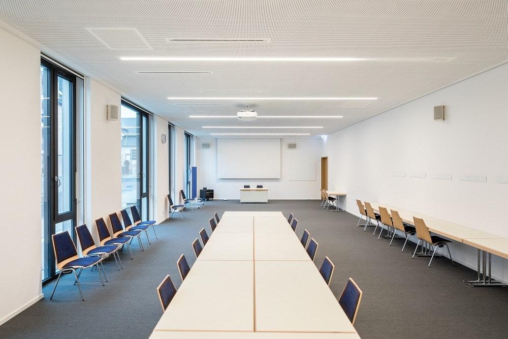Seminarraum 106 mit Beamer, Leinwand, Technik-Rack und Bose-Lautsprechern