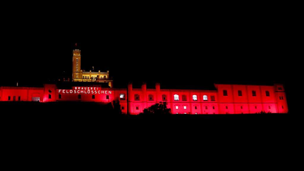 rot illuminierte Brauereigebäude der Feldschlösschenbrauerei in Rheinfelden