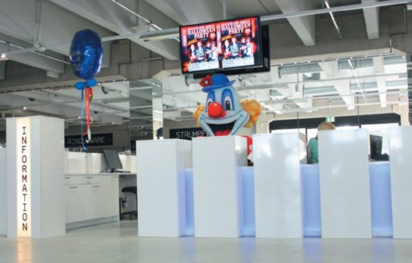 Die Displays über dem Informationsbereich begrüßen die Kunden schon beim Betreten des Shops