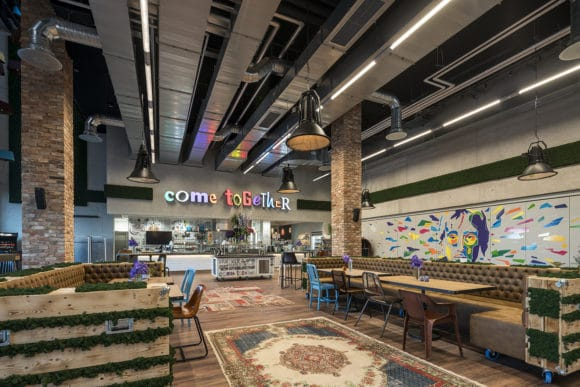 """Im Betriebsrestaurant """"Come Together"""" trifft Industrial Style auf individuell zusammengestellte Möbilierung in warmen Farben."""