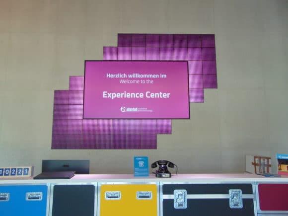 """Der Empfangstresen besteht aus farbigen Flightcases - das 85"""" Wellcome-Display ist von vierzig stufenförmig angeordneten Cameo LED Kling Tiles umgeben."""