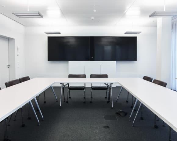 """Seminarraum mit dreitüriger Möbelvariante für 2 × 84"""" Displays"""