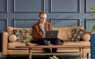 Man arbeitet im Home Office auf der Couch mit dem Laptop