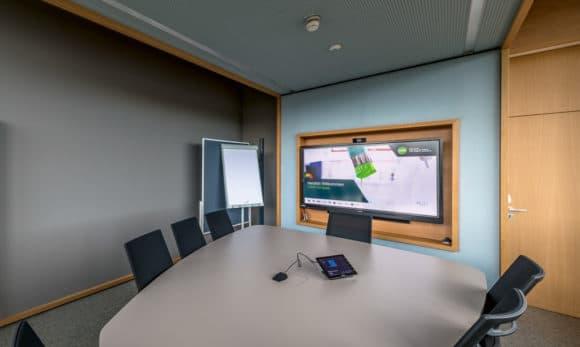Videokonferenzraum mit Bildschirm von Sharp und Konferenztisch