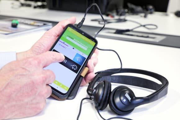 Smartphone mit Listen EVERYWHERE App und angeschlossenen Kopfhörern