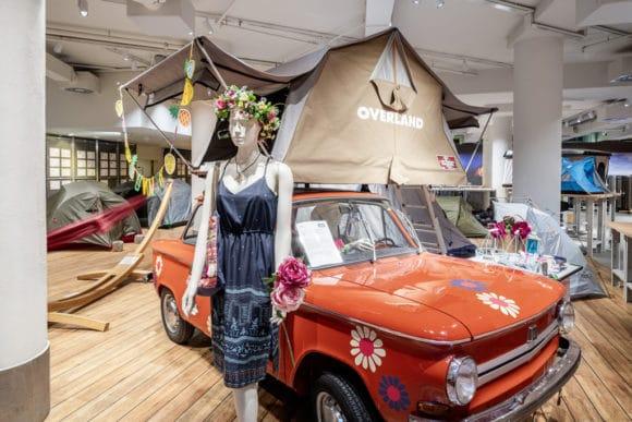 Beleuchtete Ausstellungsfläche mit Kleinwagen und Dachzelt