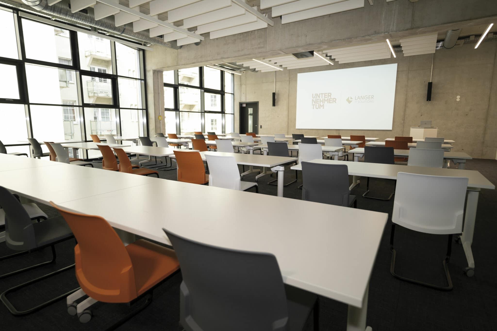 Seminarraum mit Leinwand vor den Stühlen und Tischen