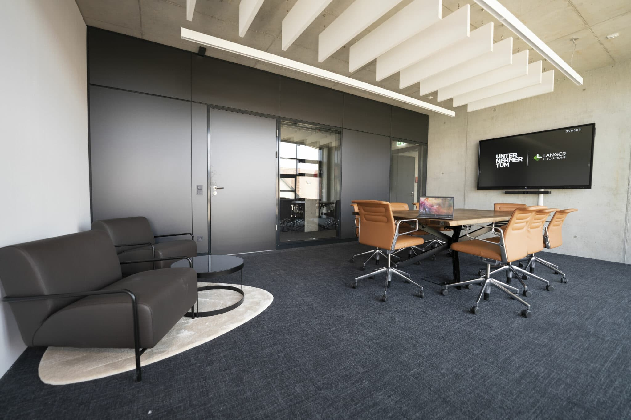 Meetingraum mit Tisch, Stühlen, Couch und Medientechnik