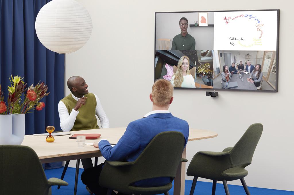 Zwei Männer in einem Konferenzraum betrachten einen anderen Mann per Videokonferenz